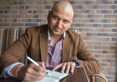 做在他的笔记本、经营计划或者日志文字的愉快的英俊的印地安商人有些笔记 库存图片