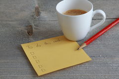 做在黄色便条纸的名单与铅笔和咖啡 库存照片