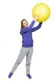 做在黄色球的女孩exersises 库存照片