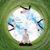 做在绿色领域的妇女瑜伽在圈子 库存照片
