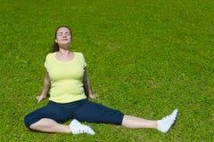 做在绿草的愉快的少妇锻炼 库存照片
