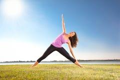 做在绿草的美丽的少妇瑜伽锻炼 免版税库存照片