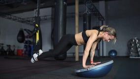 做在Bosu和TRX的黑运动服的妇女俯卧撑在健身房 影视素材