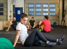 做在Crossfit健身房的妇女放松锻炼 免版税库存图片