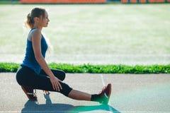 做在sadium的一件蓝色衬衣和绑腿的健身女孩准备惯例在训练前,舒展身体干涉 女性ath 库存图片