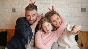 做在Smarthphone的幸福家庭画象Selfie户内 他们度过这好天气在咖啡馆 股票录像