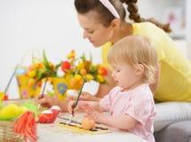 做复活节装饰的母亲和婴孩 库存图片