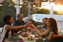 做多士的两对夫妇在晚餐在屋顶大阳台 免版税库存照片