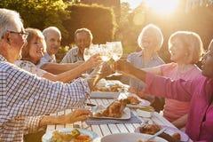 做多士的小组资深朋友在室外晚餐会 图库摄影