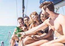 做多士的小组朋友在小船 免版税库存图片