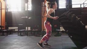 做大轮胎的坚强的健身妇女翻转在健身房的锻炼 股票视频