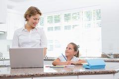 做她的与母亲的小女孩家庭作业使用膝上型计算机 库存照片