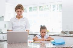 做她的与母亲的小女孩家庭作业使用膝上型计算机 图库摄影