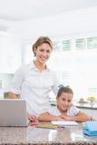 做她的与母亲的小女孩家庭作业使用膝上型计算机 免版税库存图片