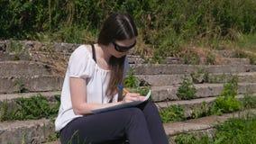 做她的任务和家庭作业的女孩坐在公园 大学生 影视素材