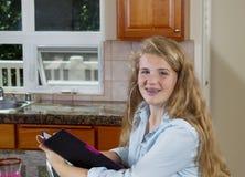 做她的家庭作业的十几岁的女孩,当听到音乐时 图库摄影