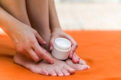 做她的脚beautifuls的妇女, apllying一些润湿的奶油用她的手,橙色背景 免版税图库摄影