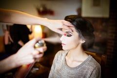 做她的头发和构成的美丽的新娘 在她的updo的发式专家喷洒的喷发剂 免版税库存图片