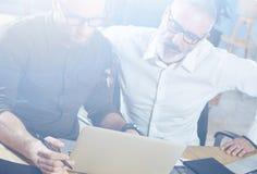 做好主意的小组两个伙伴在工作过程中在现代办公室 年轻有胡子商人做 库存照片