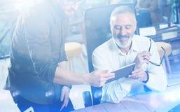 做好主意的小组两个伙伴在工作过程中在现代办公室 观看流动片剂的成人有胡子的人 库存照片
