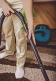 做妇女差事的年长妇女 Vacumming地毯 免版税库存照片