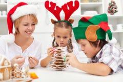 做姜饼曲奇饼圣诞树的愉快的家庭 库存图片