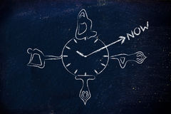 做姿势的信奉瑜伽者在现在表明的时钟附近 库存照片