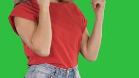 做姿态的红色T恤杉的妇女,当谈话在一个绿色屏幕,色度钥匙上时的电话 影视素材