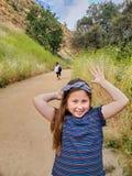 做嬉戏的面孔的妇女和女儿,当一起走在一条足迹或土路在森林在一个黄色领域旁边时 免版税库存图片