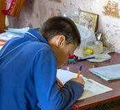 做学校家庭作业的11岁的男孩少年 库存照片
