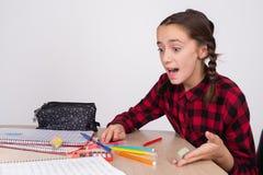 做学校的家庭作业的惊奇的和恼怒的女孩 库存图片