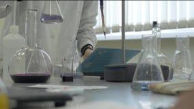 做实验的化验员在实验室 男性医疗或科学实验室研究员执行测试与蓝色液体 影视素材