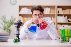 做实验的疯狂的疯狂的科学家医生在实验室 免版税图库摄影