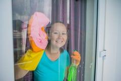 做家事的美丽的女性佣人,当曾经浪花,洗涤的窗口时 库存图片