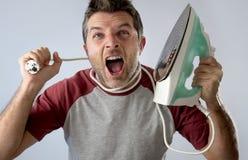 做家事的年轻疯狂的绝望和沮丧的人拿着铁 免版税库存照片