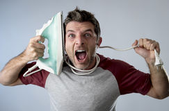 做家事的年轻疯狂的绝望和沮丧的人拿着铁 免版税库存图片