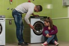 做家事洗衣店的年轻夫妇 免版税库存图片