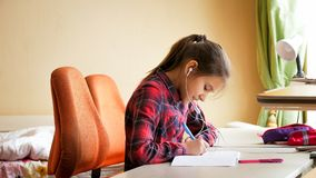 做家庭作业和听的音乐的微笑的十几岁的女孩画象  免版税库存照片