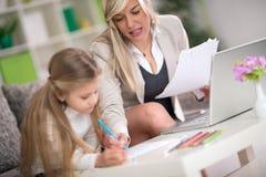 做家庭作业在妈妈的帮助下的女儿 免版税库存照片