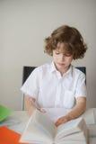 做家庭作业的一件白色衬衣的男小学生 免版税库存图片