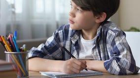 做家庭作业的乏味男小学生,看起来外部窗口以遗憾,特写镜头 影视素材