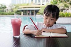 做家庭作业的亚裔中国小女孩 免版税库存照片