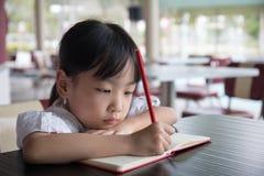 做家庭作业的亚裔中国小女孩 免版税图库摄影