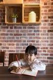 做家庭作业的亚裔中国小女孩 免版税库存图片