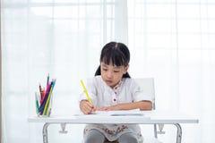 做家庭作业的亚裔矮小的中国女孩 库存图片