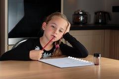 做家庭作业的作白日梦的女孩 库存照片