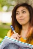 做家庭作业的女学生在公园 免版税库存照片