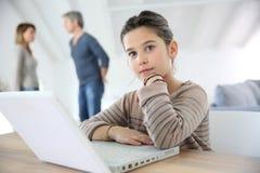 做家庭作业的女孩使用膝上型计算机 免版税图库摄影