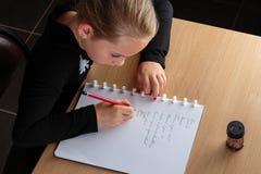 做家庭作业的女孩在厨房里 免版税库存照片
