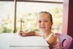 做家庭作业的女孩在教室 免版税库存照片